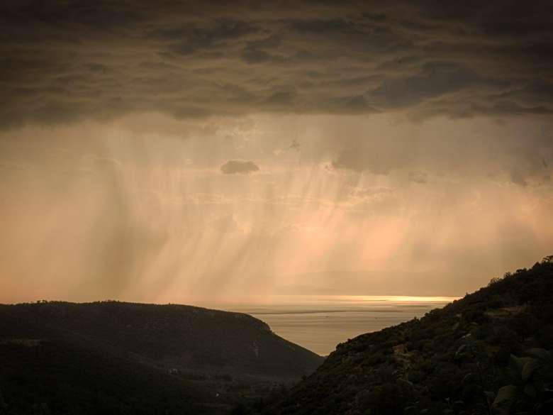Sonnenuntergang mit starkem Regen über dem Meer Ende September.