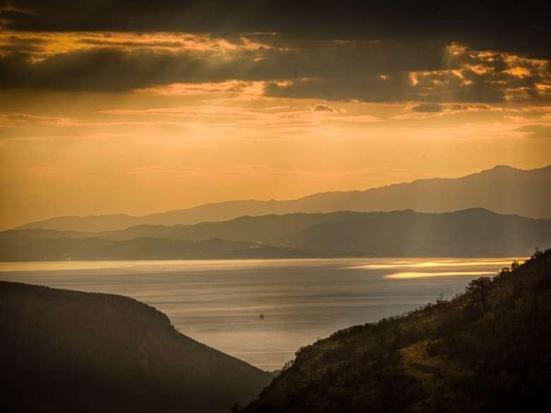 Goldene Lichtstimmung bei einem Sonnenuntergang mit Lichtflecken auf dem Meer im Frühling.